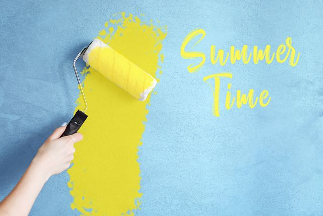 Cropped image of a hand holding a paint roller while painting a house wall in yellow with the inscription summer time.