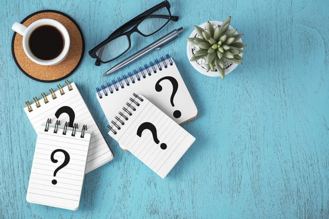 Question marks on notepads on blue wooden desk, variety of questions, faq concept