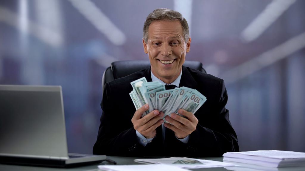 Greedy businessman holding bunch of dollars, rejoicing easy income