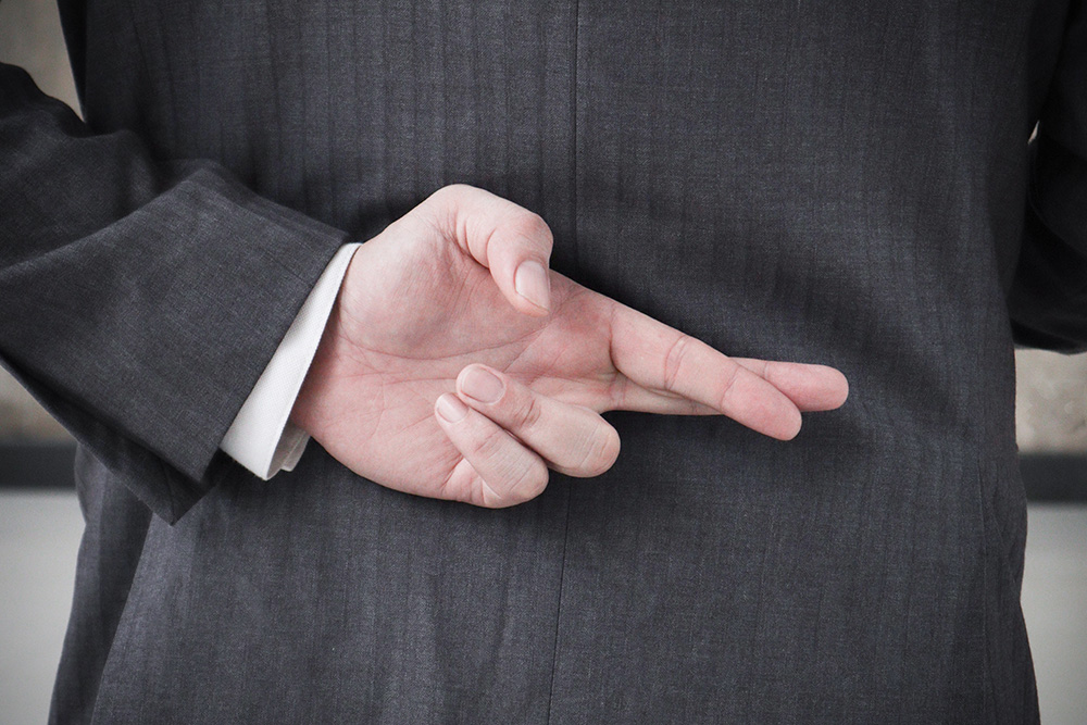 Businessman with his fingers crossed behind his back