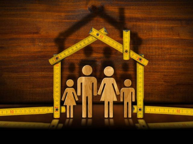 family illustrated under an outline of a house using measuring tapes with a wooden background.