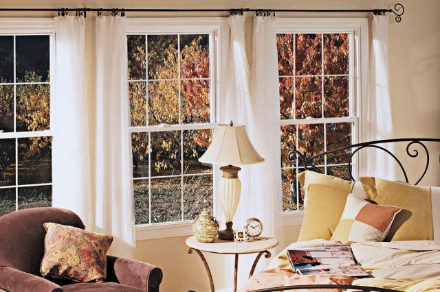 Image of beautiful triple pane windows in a cozy bedroom with white frames, flowing white curtains, and clean energy efficiency glass that were installed in the St. Louis Metro area by XteriorPRO.